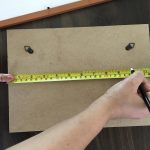 Step 2 Before you hang a large picture frame, use a measuring tape to mark the places where you will install the beta steel tapes.